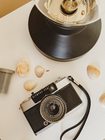 picture of olympus pen ees-2 camera and seashells next to a vintage lamp