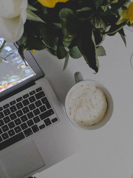 image of a freelancer's laptop, coffee and flowers on a desk seen from above