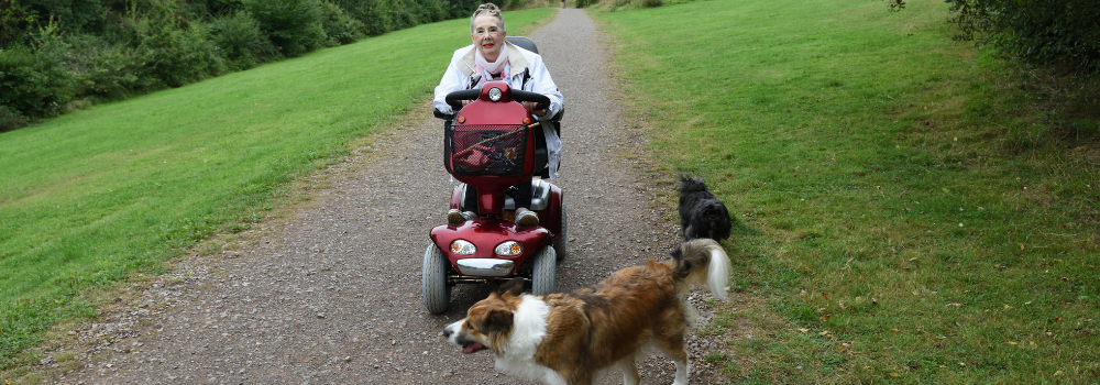 Woman riding red mobility scooter with dog on park trail