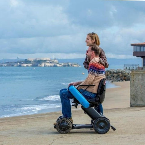 Image of Couple Enjoying A Beach Walk While Man Rides WHILL Model Ci Travel/Portable Power Wheelchair 210-06874