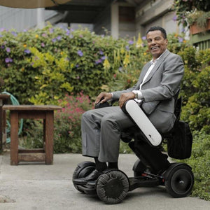 Man Smiling While Riding WHILL Model Ci Travel/Portable Power Wheelchair 210-06874