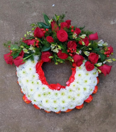 Executive red round shaped funeral wreath by Simona Flowers