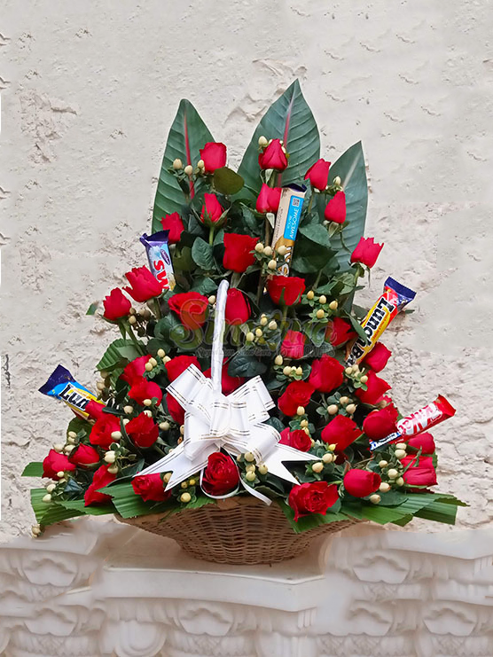 Scrumptious basket of red roses and chocolates by Simona Flowers