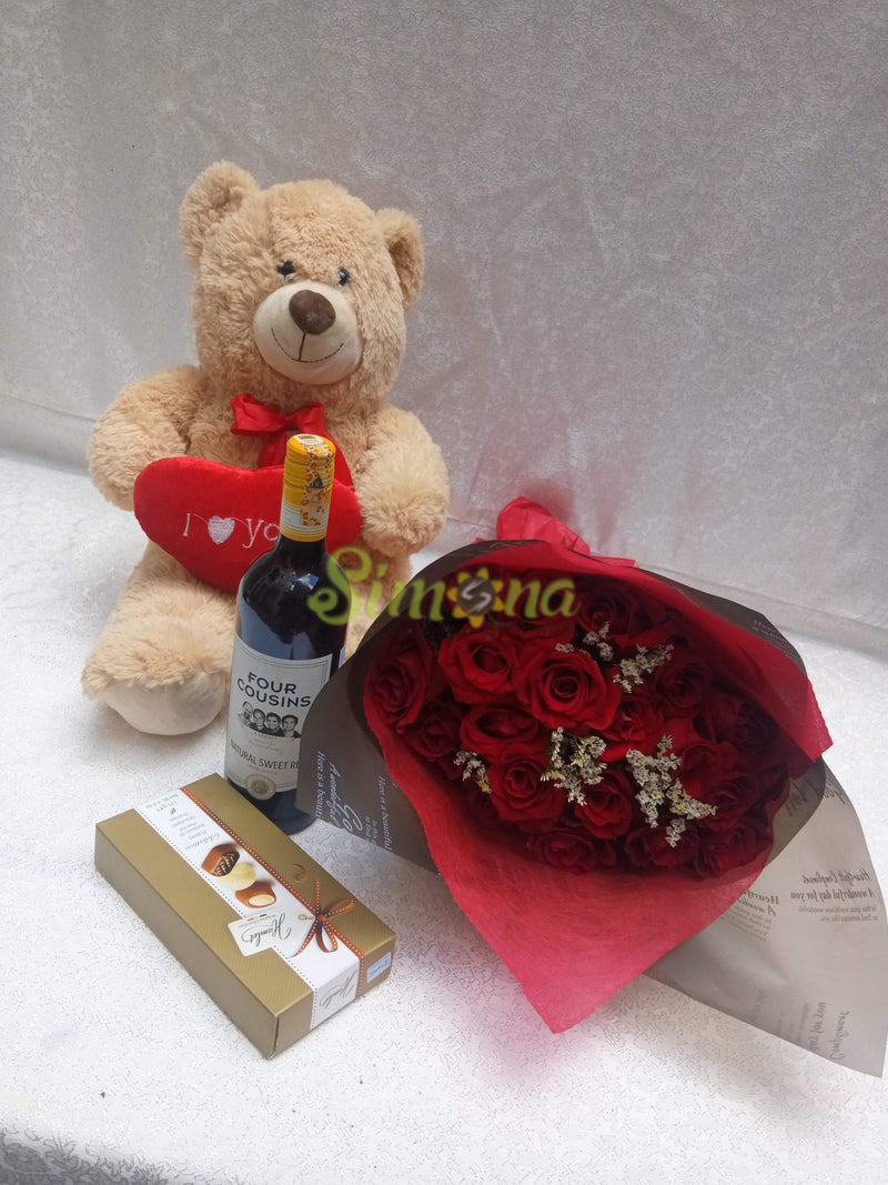 Delightful hand bouquet with teddy bear, red wine and hamlet chocolate