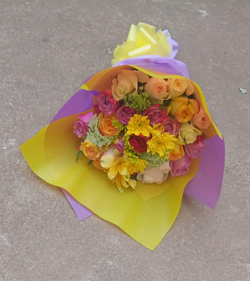 A hand bouquet of roses and a touch of chrysanthemums with complimenting flower fillers