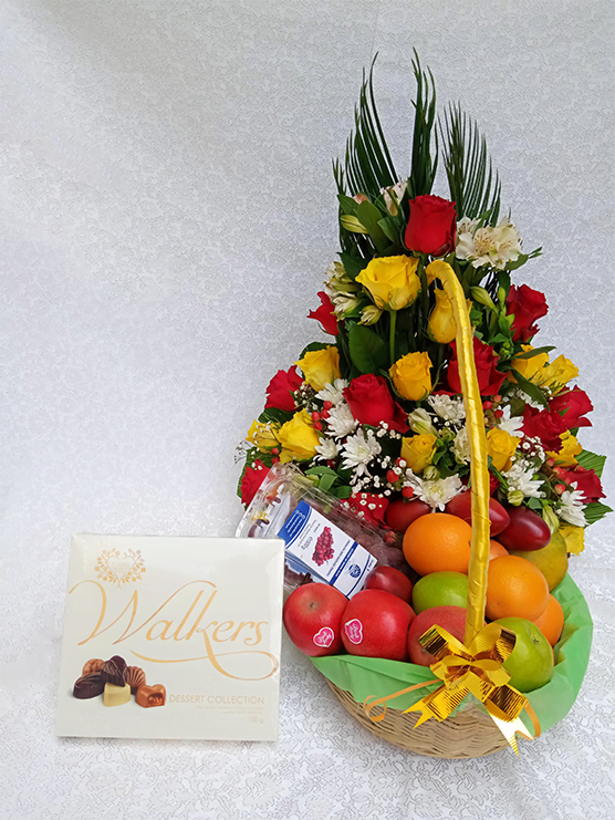 Flowers and fruits in a basket sided with a chocolate