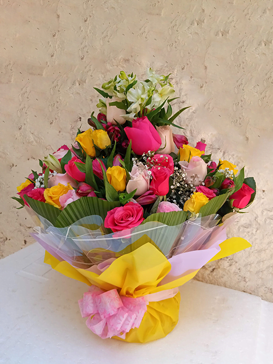 Adorned water bouquet flower arrangement of roses and various flower fillers an beautiful wrapping.