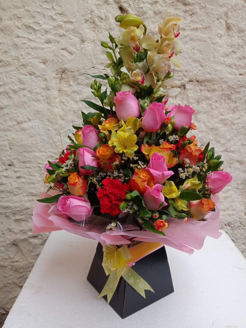 A royal box flower arrangement of orchids, roses and a touch of tropical flower fillers