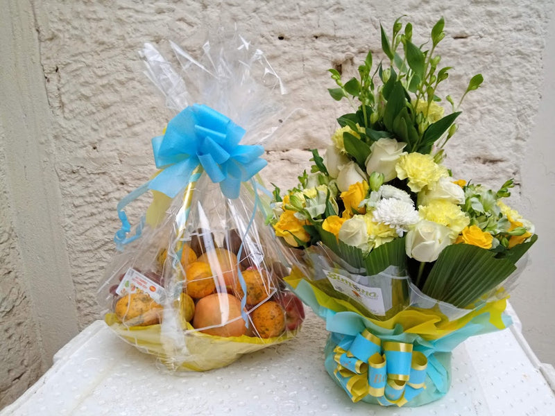 A package of an assorted fruit basket and flower arrangement