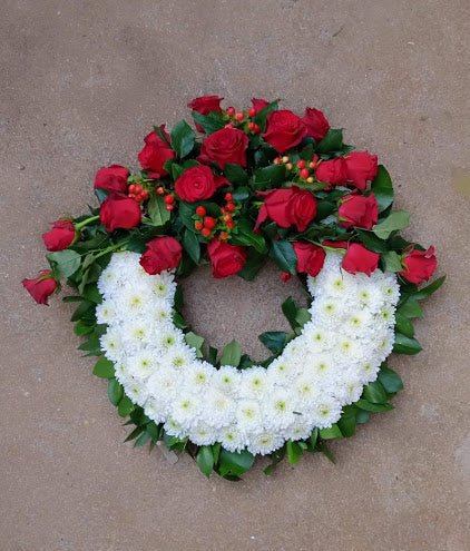 Executive ruby red rose round funeral wreath by Simona Flowers