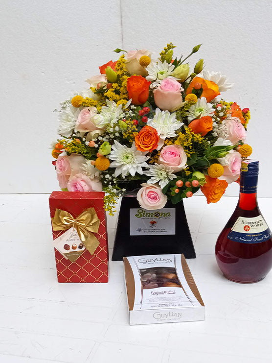 The full of joy package with A royal box flower arrangement, Red Robertson wine and two boxes of Guylian chocolates by Simona Flowers