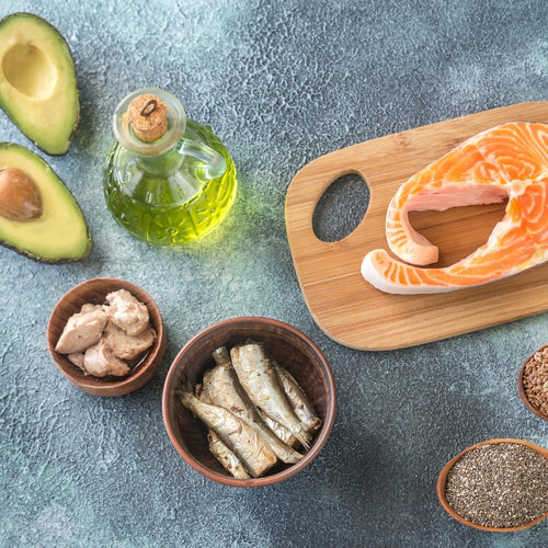 Image: Different foods on the kitchen side - avocados, oil, oily fish and seeds. Omega-3s.