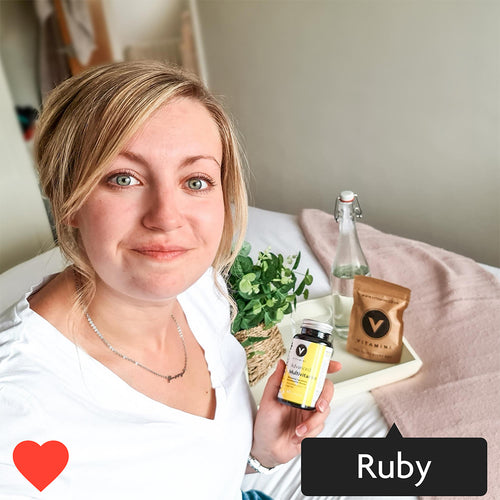 Instagram style image with Ruby tagged in. Ruby is holding a pot of Vitamini Women's Multivitamins. Ruby is smiling and has an eco-pouch and bottle of water on the side.