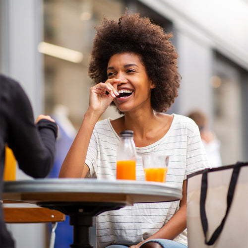 Woman of colour sitting at an outside table with another person. There is a juice bottle and glass of juice on the table and the woman is laughing / smiling / feeling good.