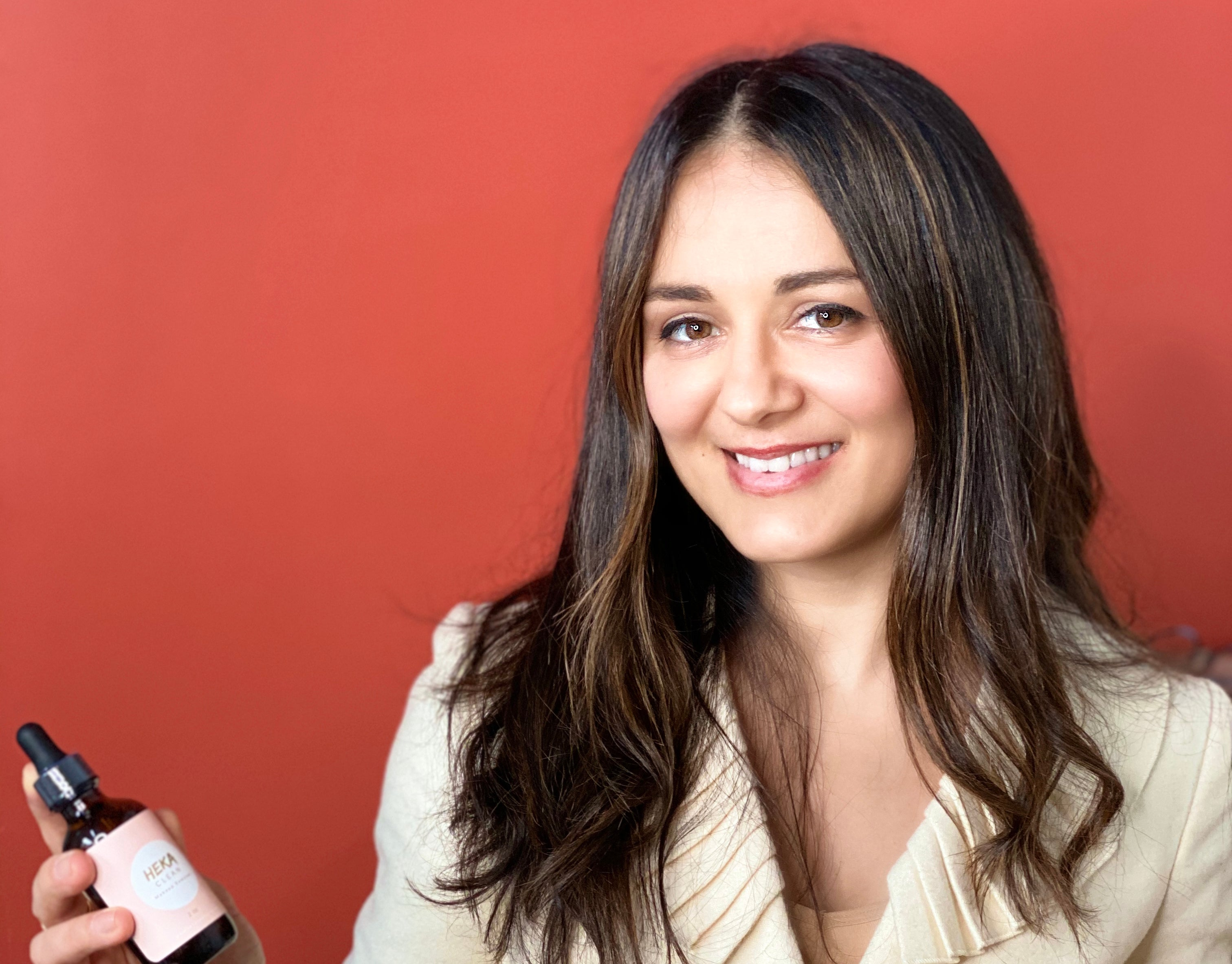 Dr. Mila Ioussifova holding a bottle of HEKA Clean Makeup Remover.