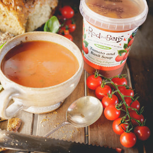 A bowl of Rod & Ben's organic fresh Tomato and Basil soup next to the pot, with fresh tomatoes and bread. The pot shows the soup to be gluten free, dairy free, vegan and organic.