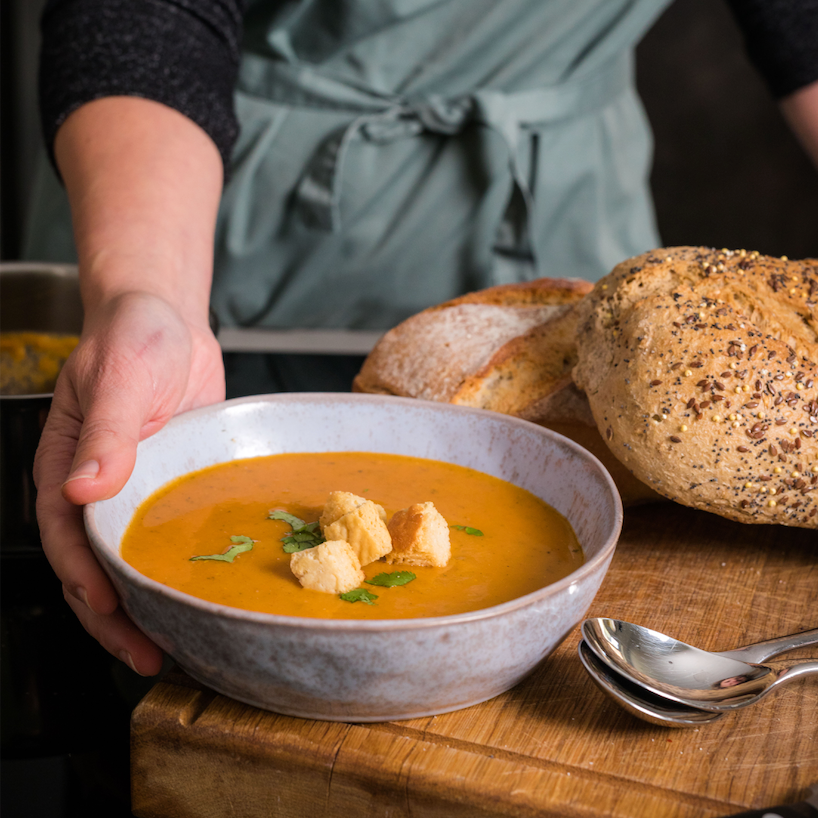 A rustic bowl of organic Rod & Ben's lentil soup with croutons and herbs, placed on a  wooden chopping board with fresh bread.