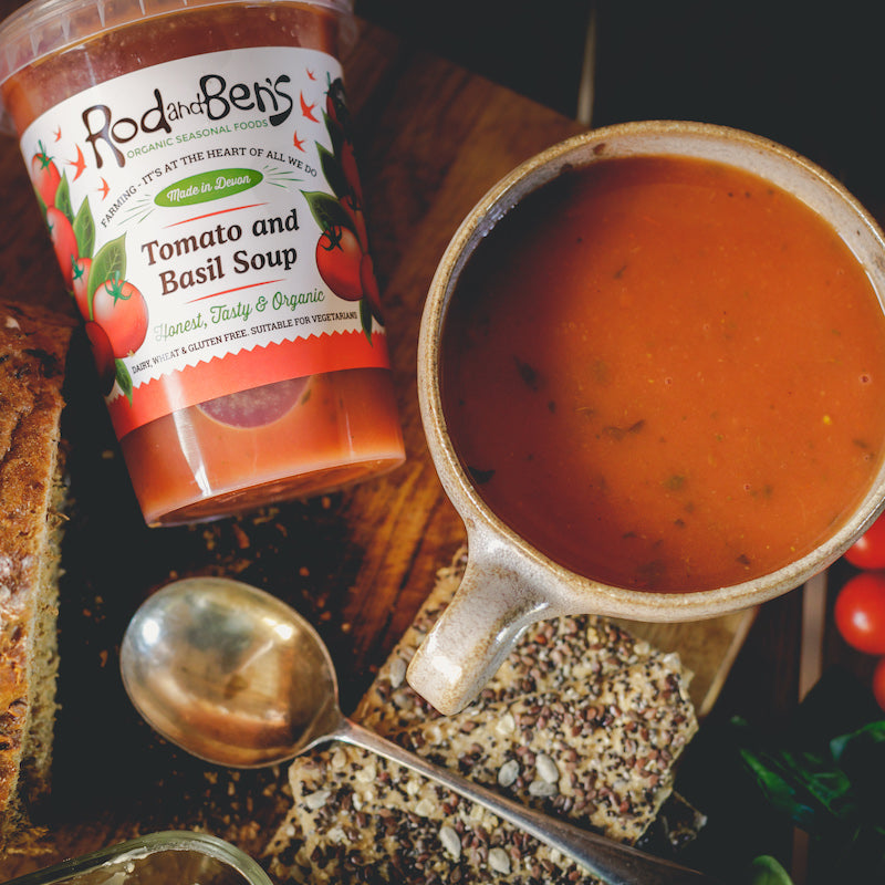 A bowl of Rod & Ben's organic fresh Tomato and Basil soup next to the pot, with seeded crackers and fresh tomatoes. The pot shows the soup to be gluten free, dairy free, vegan and organic.