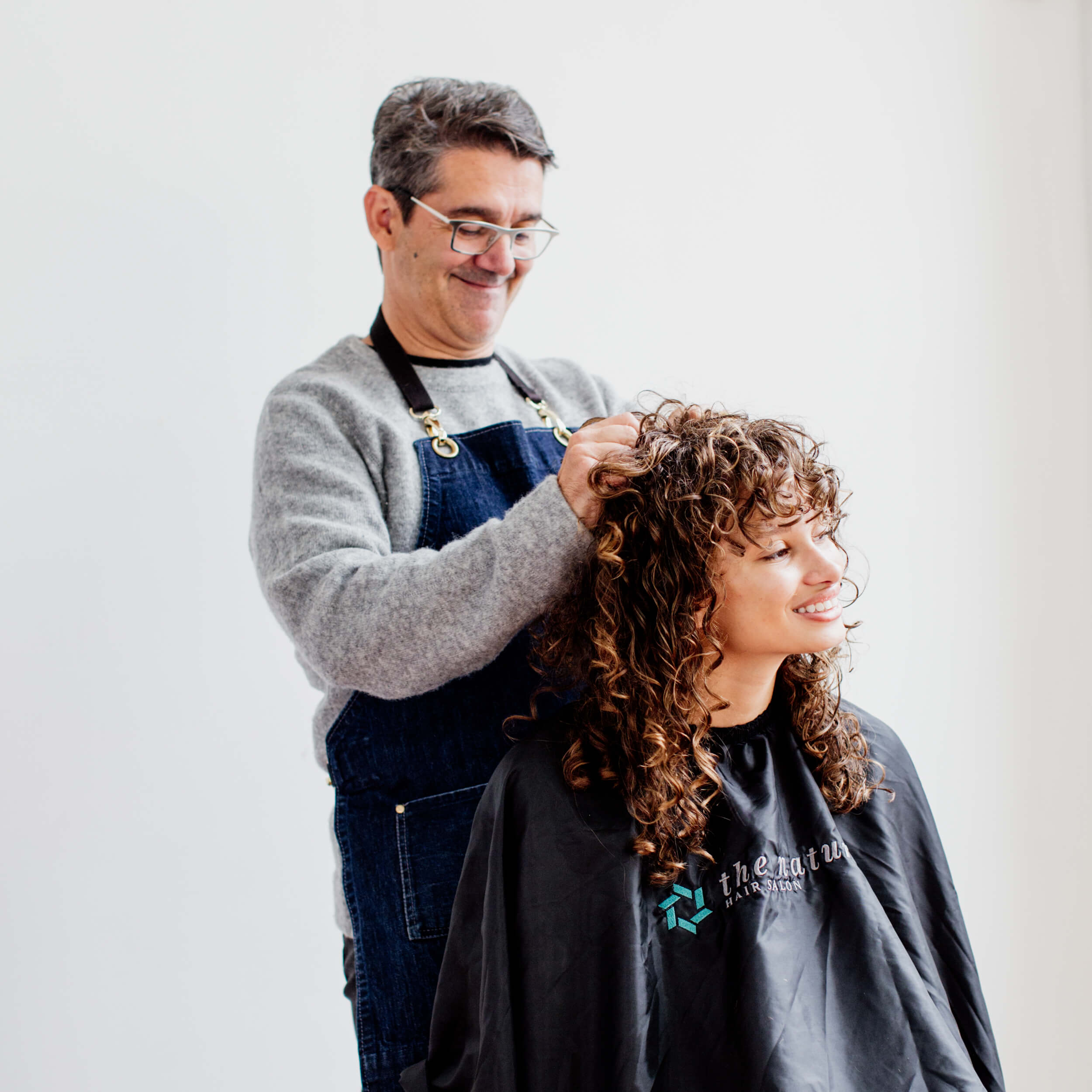 A hairdresser works on a client's hair.