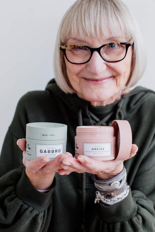 A woman holds some jars of hair product.