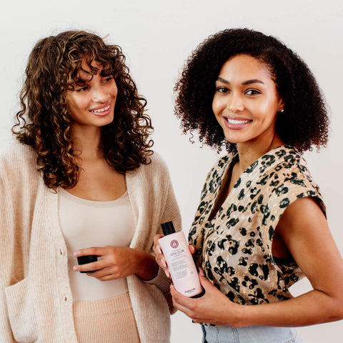 Two women with curly hair stand together.