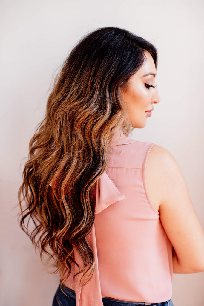 Woman is showing us her hair extensions, she is wearing a pink blouse
