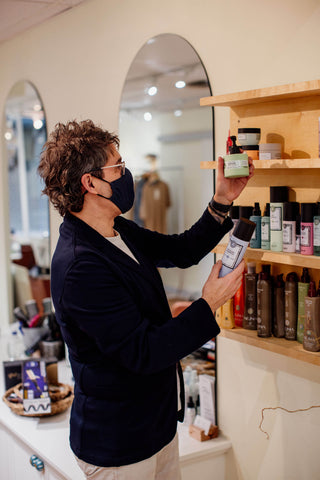 The owner of a hair salon looks at hair products.