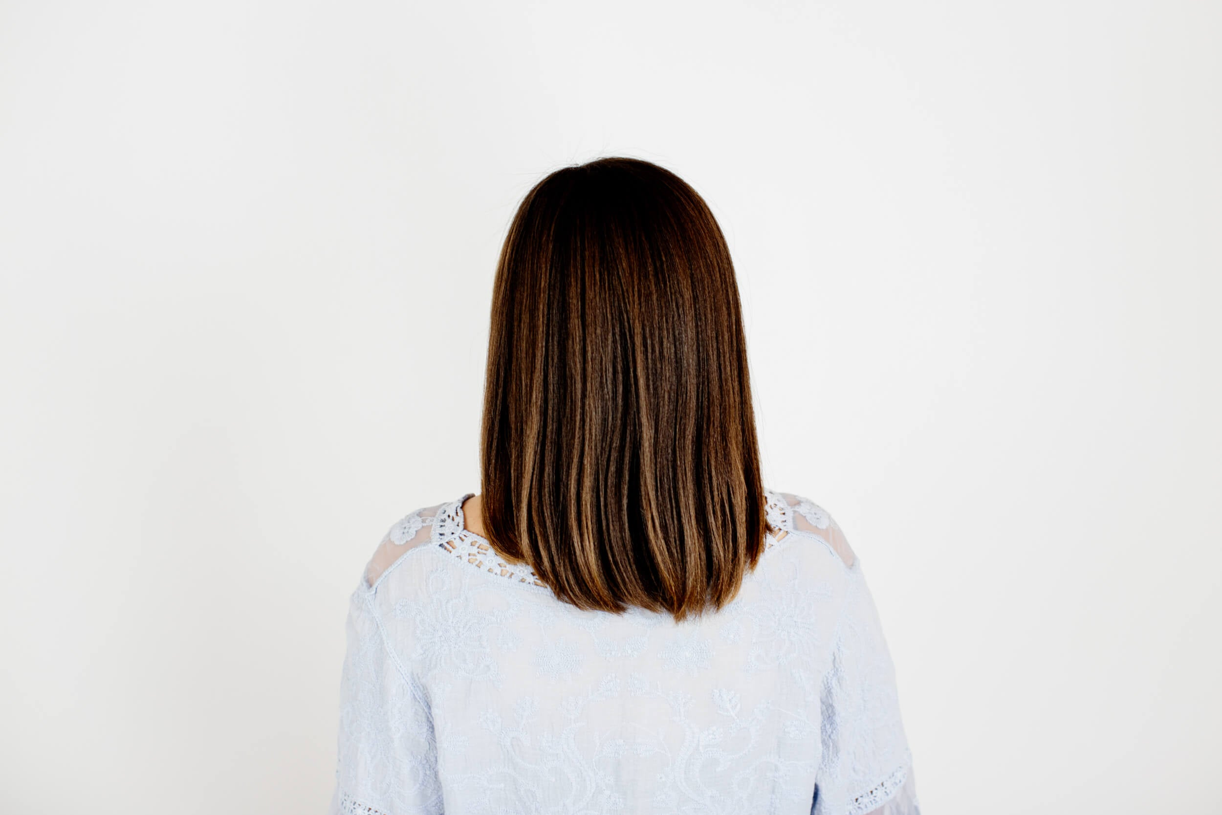 A woman shows the back of her hair that has been straightened.