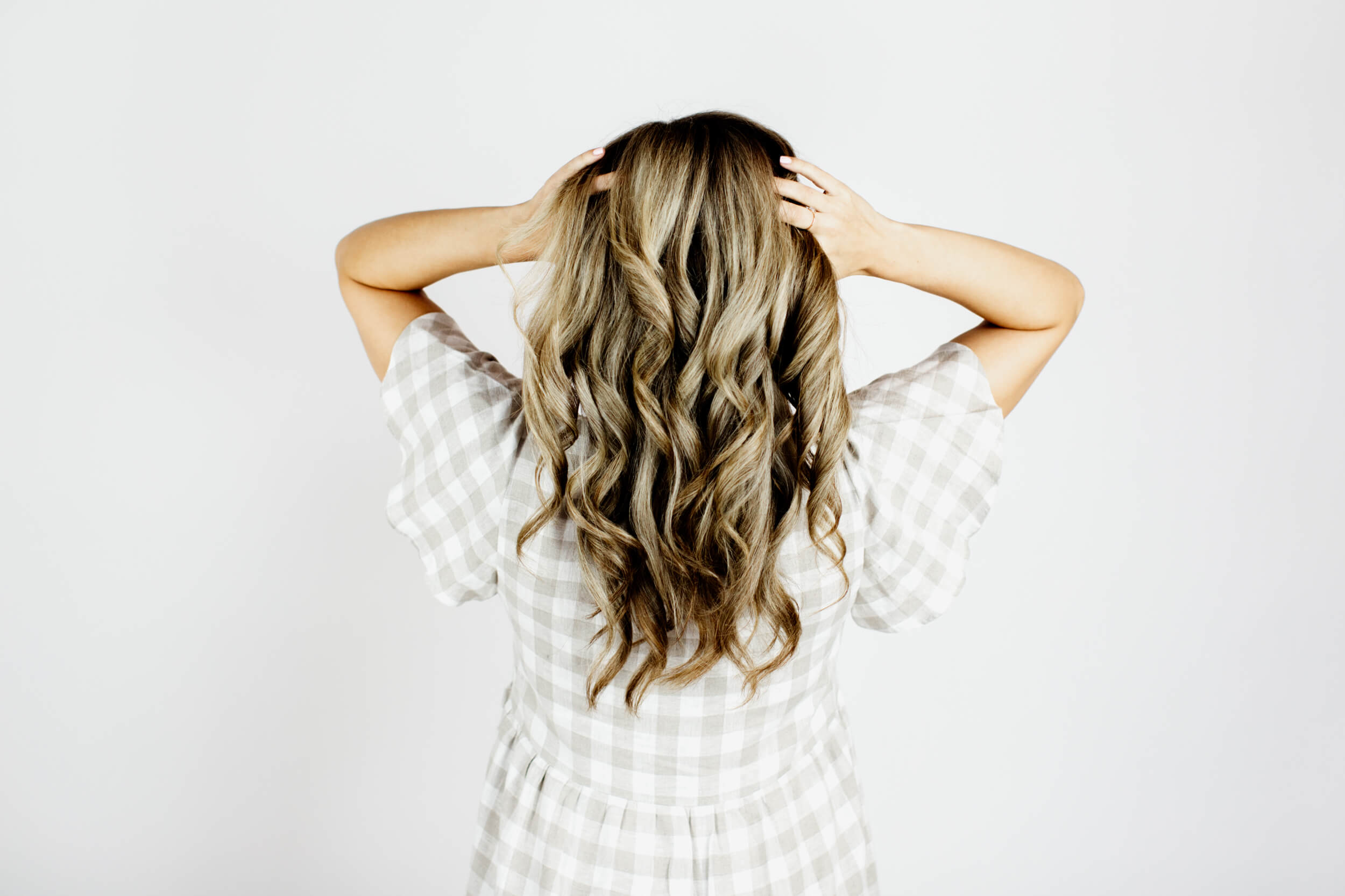 A head of curly blonde hair seen from the back.