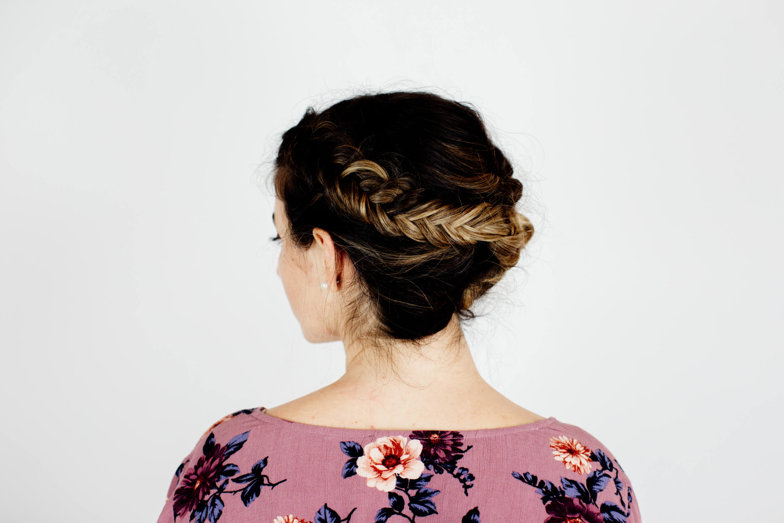 A woman wearing an intricate braid in her hair seen from the back.