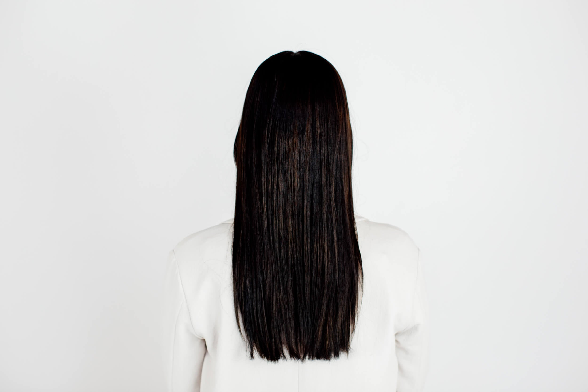 A woman with straight black hair as seen from the back.