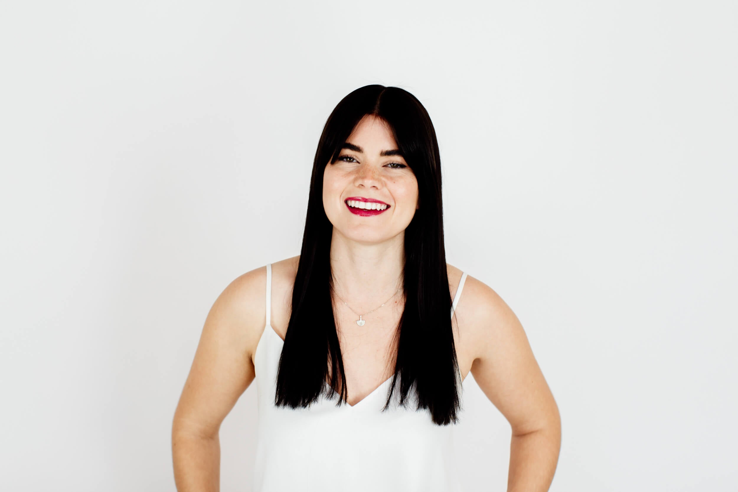 A woman with long black hair smiles at the camera.