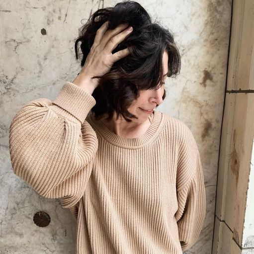 Woman is holding her hair, wearing a stylish full sleeve sweatshirt