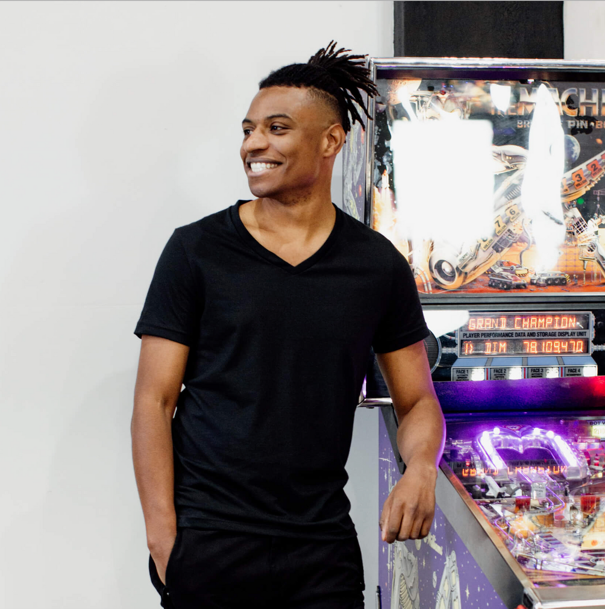 Man is smiling and leaning on a pinball machine wearing V-neck Citizen goods black t-shirt and CP black cargo pants