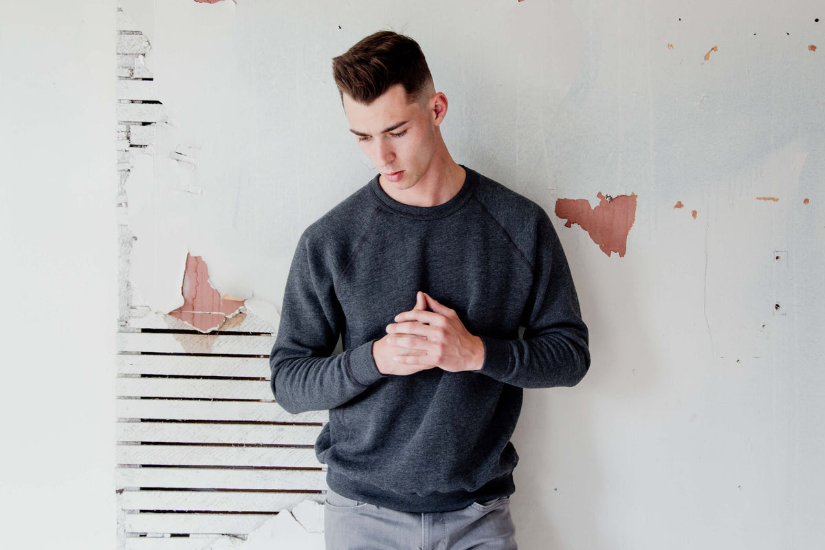 Man wearing grey crewneck and grey jeans. He is leaning on a white wall.