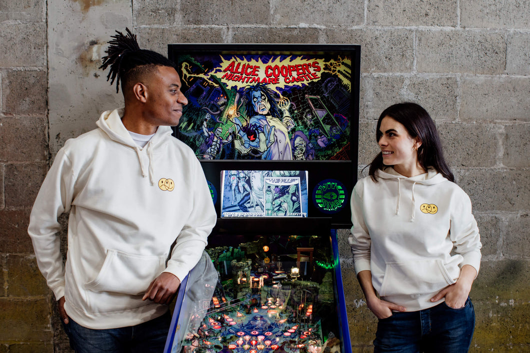 A man and woman looking at each other and leaning on a pinball machine wearing cream colour hoodies with a smiley face graphic on top left