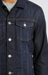 man is wearing a dark denim jean jacket that is fitted and has slight stretch
