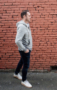 man is wearing grey zip up hoody and jeans