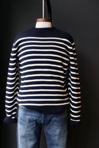 mannequin is wearing a merino wool ribbed Brenton  sweater with mid wash denim jeans