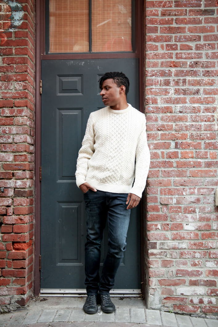 man is wearing a cream coloured fisherman knit sweater and black stone washed jeans
