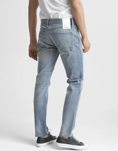 Load image into Gallery viewer, man is wearing a light wash stretch denim jean