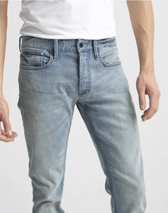 man is wearing a light wash stretch denim jean