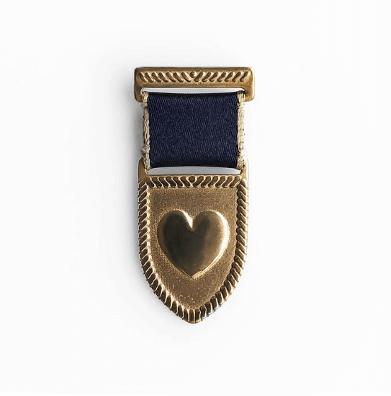 handcrafted heart medal brass with a navy/gold ribbon