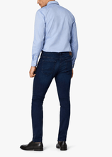 Load image into Gallery viewer, Man is wearing a rich indigo mid rise tapered leg jean. Best fitting premium denim dark wash jeans for men made in Turkey