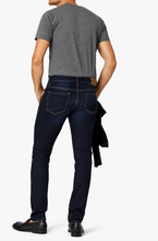 Load image into Gallery viewer, man is wearing a dark denim that tapers at the  knee and is mid rise