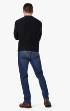 Load image into Gallery viewer, Man is wearing a washed denim jean that is mid rise and has a tapered leg from the knee down