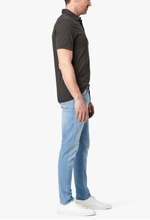 Load image into Gallery viewer, man wearing light denim jeans with white sneakers