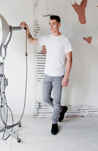 Load image into Gallery viewer, Everyday best organic cotton and recycled polyester white t-shirt for men.man is wearing a white Citizen Goods t-shirt, grey Denham jeans, and black suede boots and is standing in a factory holding an industrial light