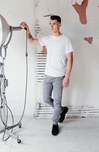 Everyday best organic cotton and recycled polyester white t-shirt for men.man is wearing a white Citizen Goods t-shirt, grey Denham jeans, and black suede boots and is standing in a factory holding an industrial light