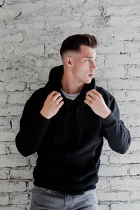 Best everyday organic cotton and recycled polyester Ecofleece black hoodie. Man is wearing a black hoodie sweatshirt and grey jeans